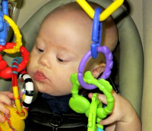 Learning to reach and grab for toys while sitting upright to strengthen head control
